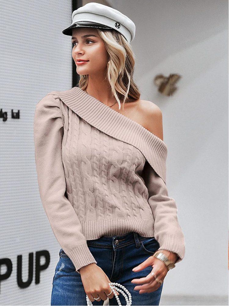 Beżowy sweter z odkrytym ramieniem i warkoczami