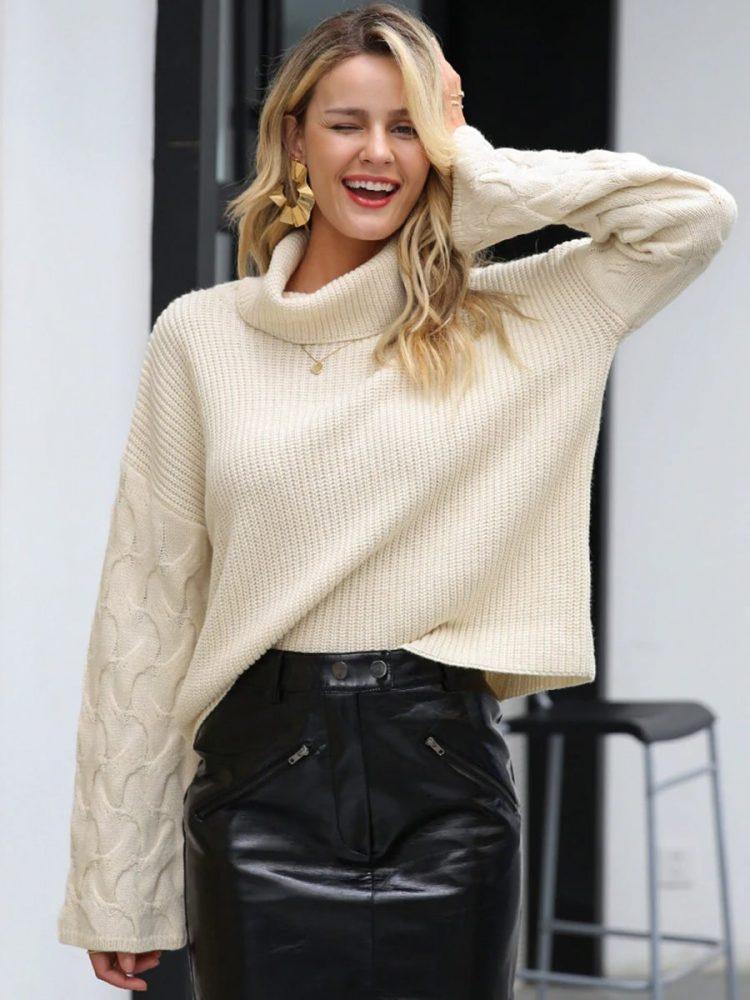 Kremowy sweter z warkoczami na rękawach i golfem