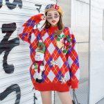 Pomarańczowy damski sweter świąteczny w romby z maskotką bałwana