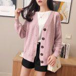 Pastelowy jasno różowy sweter typu kardigan z zapięciem na duże guziki