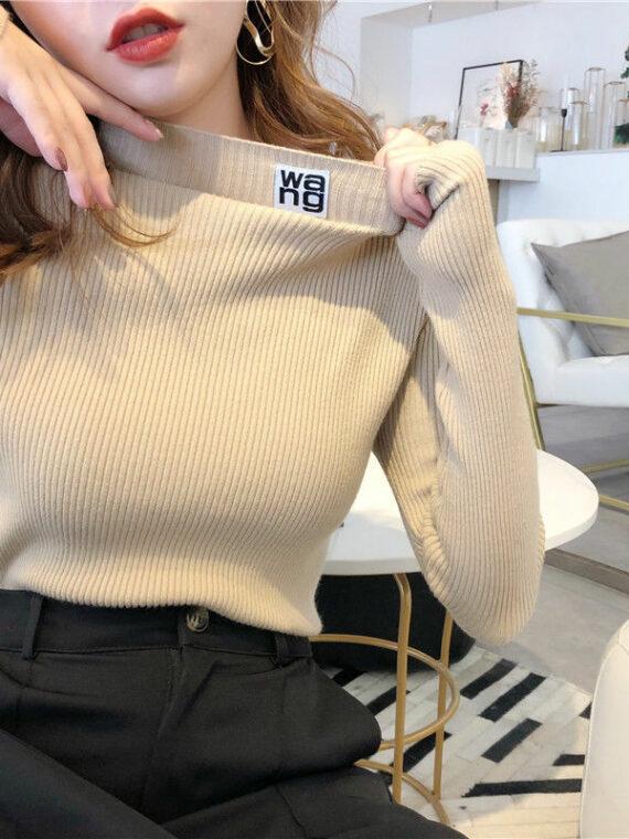 Rozciągliwy obcisły kremowy sweter z naszywką i półgolfem z prążkowanej dzianiny