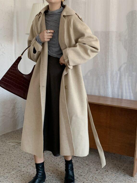 Beżowy jesienny płaszcz typu trencz z paskiem oversize